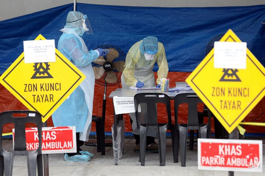 Health workers preparing to test patients for coronavirus at a clinic in Kuala Lumpur on March 23, 2020.