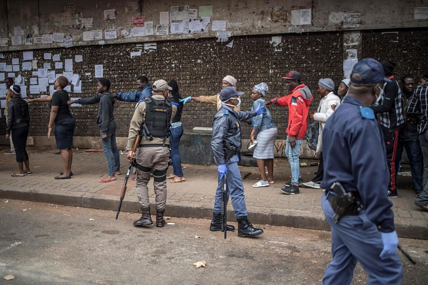 A South African police officer forcing shoppers to ensure they are at least 1m apart while queueing outside a supermarket in Yeoville, Johannesburg, on March 28, 2020.