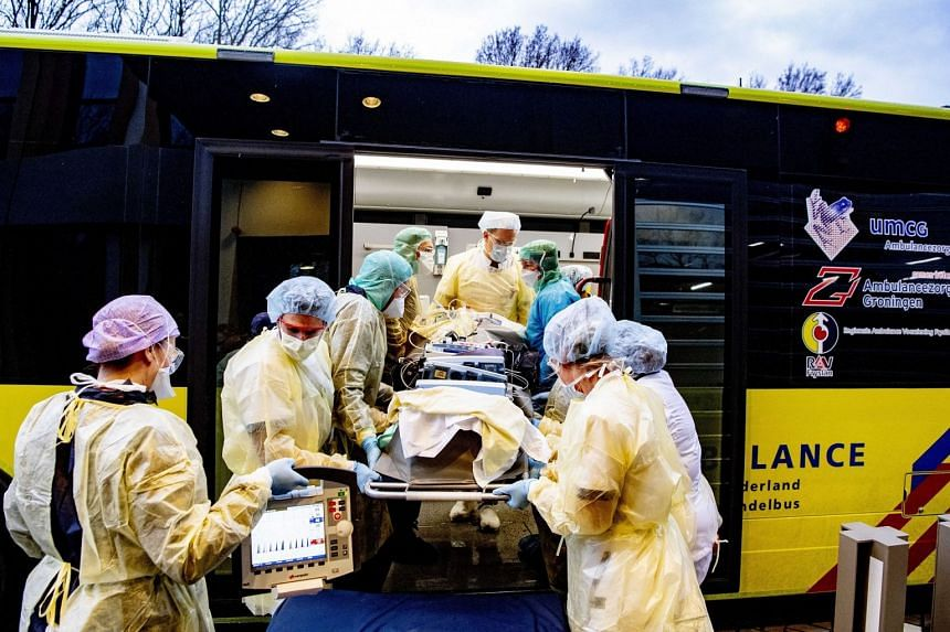 Medical personnel transfer an intensive care patient to a Mobile Intensive Care Unit vehicle in Breda, the Netherlands.