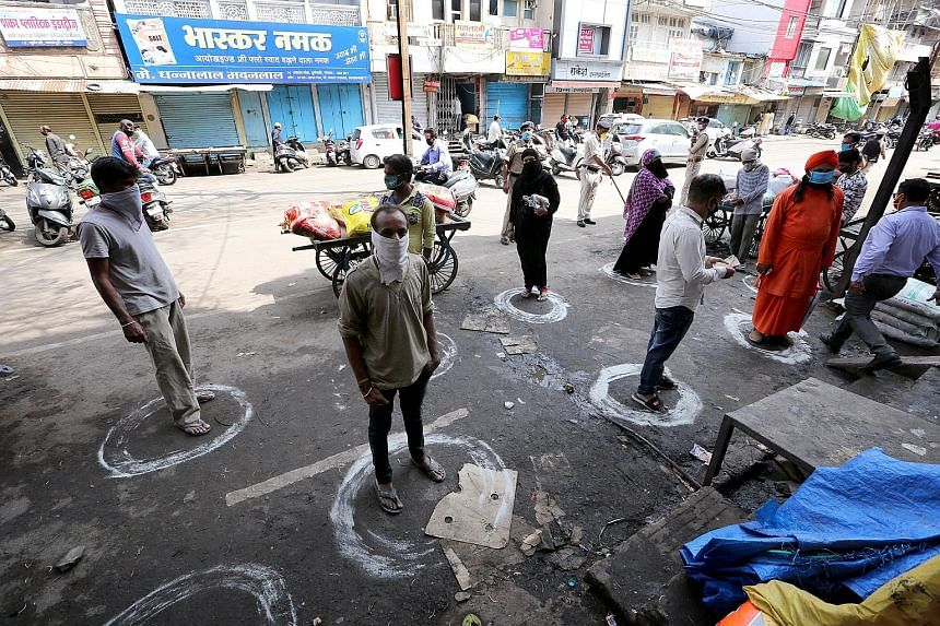 People standing in designated spots in Bhopal, India, yesterday to maintain social distancing as they queued outside a general store during a government-imposed 21-day nationwide lockdown, which has been put in place to fight the coronavirus outbreak
