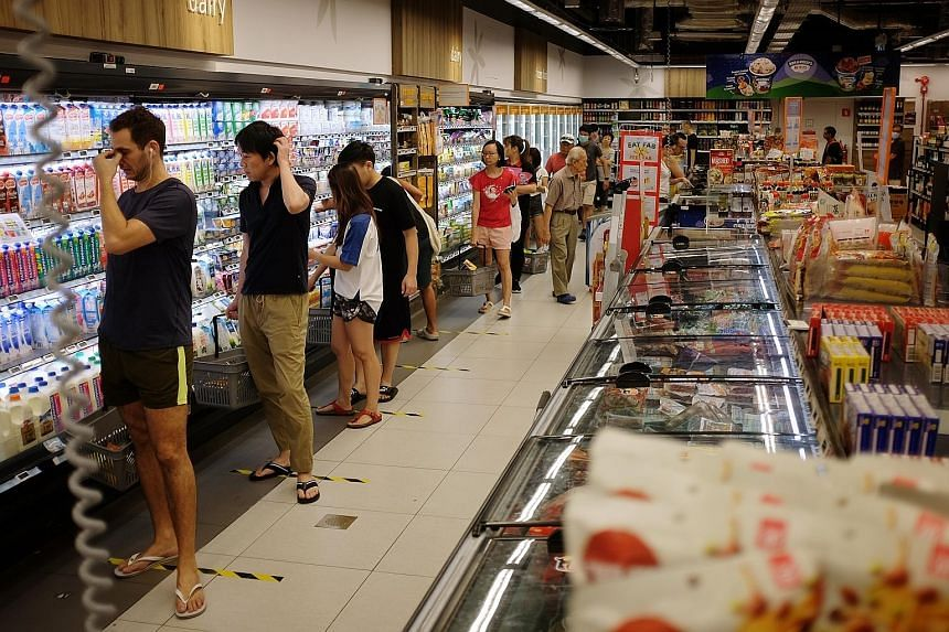 Shoppers at Tiong Bahru Plaza yesterday, the first Saturday after stricter measures were put in place to curb the spread of the coronavirus, requiring malls to limit customer numbers and disperse groups of more than 10. Left: Shoppers in a queue at a