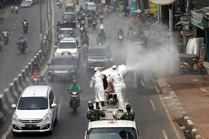 Red Cross personnel in protective suits spraying disinfectant from a vehicle in Jakarta yesterday to prevent the spread of the coronavirus outbreak. Jakarta has a total of 627 cases, and 62 people have died. PHOTO: REUTERS