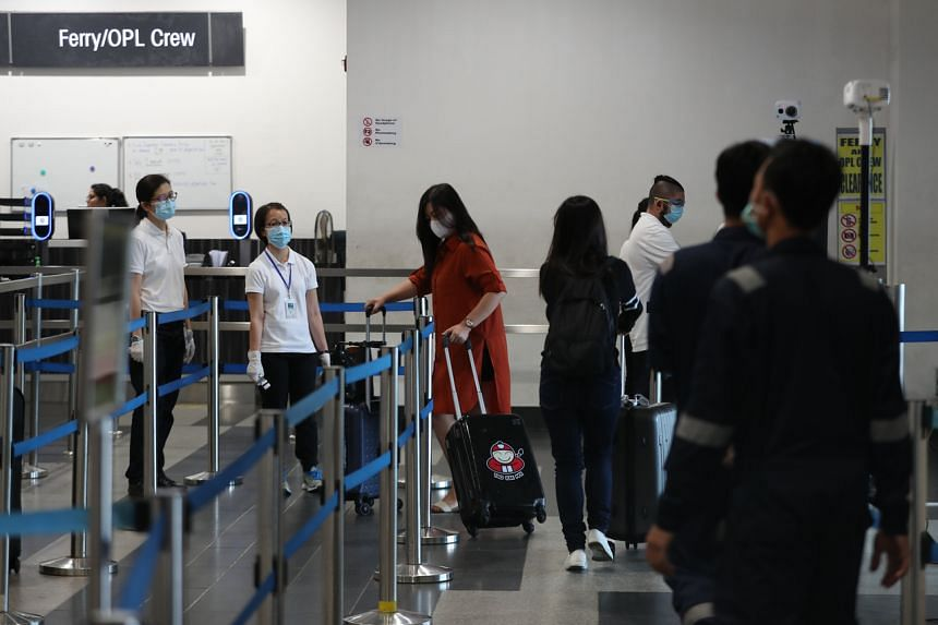 Passengers arrive at the Singapore Cruise Centre are screened by thermal scanners, on March 5, 2020.