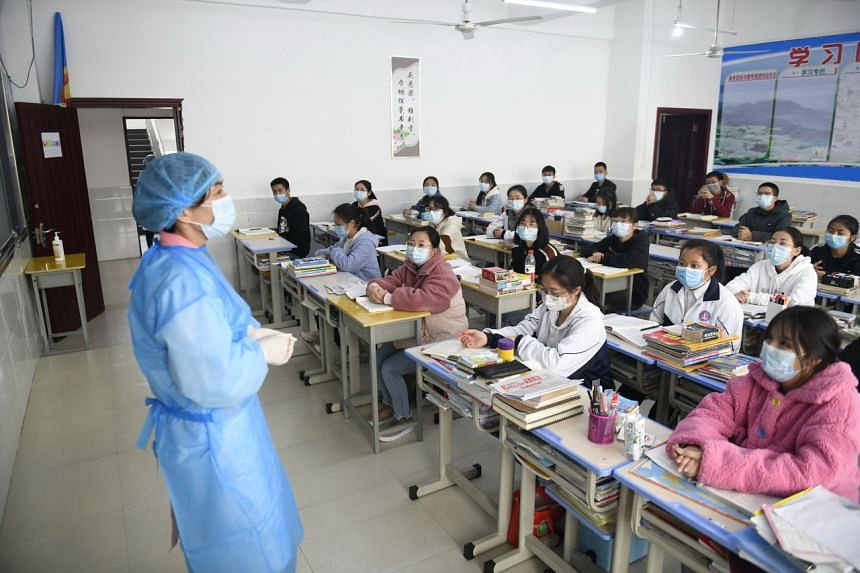 Medical staff talking to students about the coronavirus in No. 1 Middle school in Anlong county, Guizhou Province, China, on March 16, 2020.