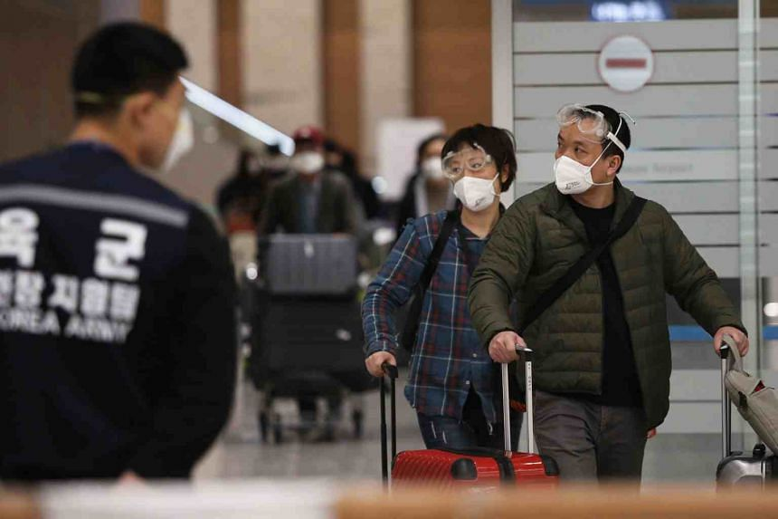 A photo taken on March 27, 2020, shows passengers with protective face masks walk to an 'Open Walking-Thru' centre for coronavirus tests at an airport in Incheon, South Korea.