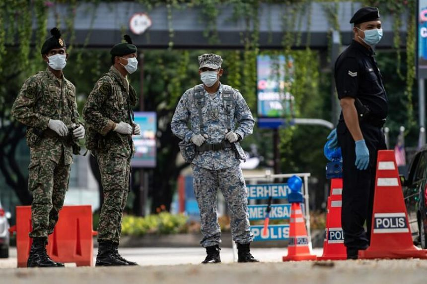 A police officer and soldiers stand at a roadblock to maintain Malaysia's movement control order in Kuala Lumpur on March 25, 2020.