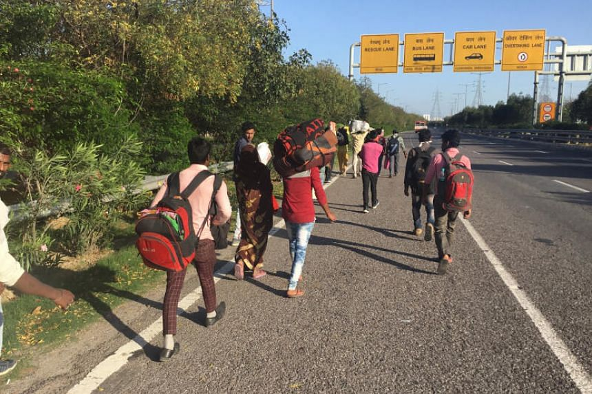 Migrants head back home on the expressway that leads from Noida, one of Delhi's satellite cities, further into Uttar Pradesh, in India, on March 28, 2020.