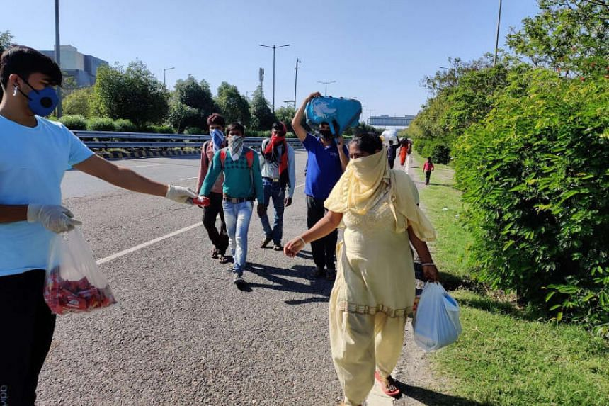 A volunteer in Noida distributing biscuit packets to migrants heading back home on on March 29, 2020.