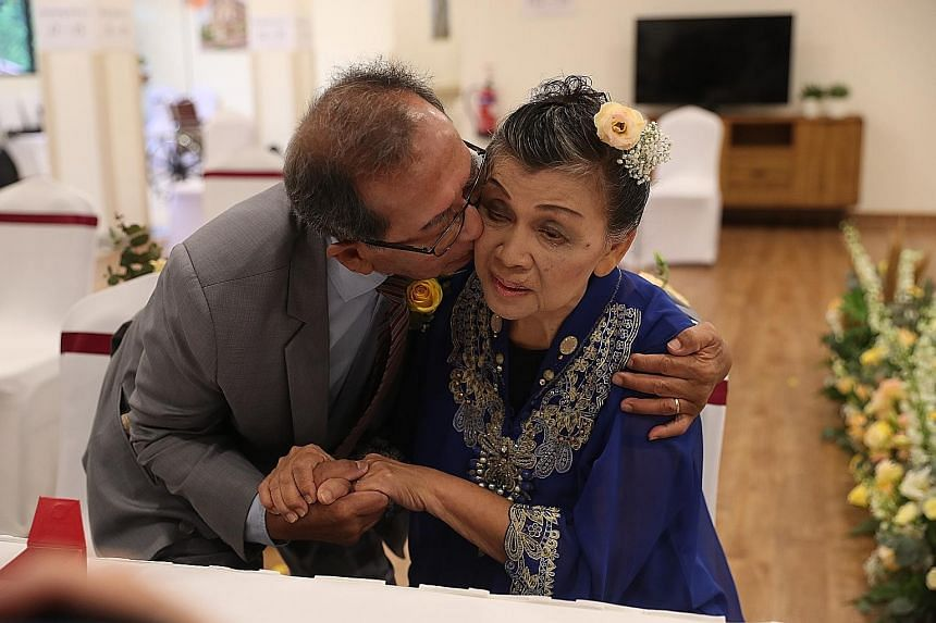 Alexandra Hospital staff giving the newly-weds a bouquet of flowers. The ceremony was organised by the hospital staff in three days. Mr Tom Iljas, 81, kissing his new bride, Madam Liong May Swan, 78, at the wedding ceremony at Alexandra Hospital on S