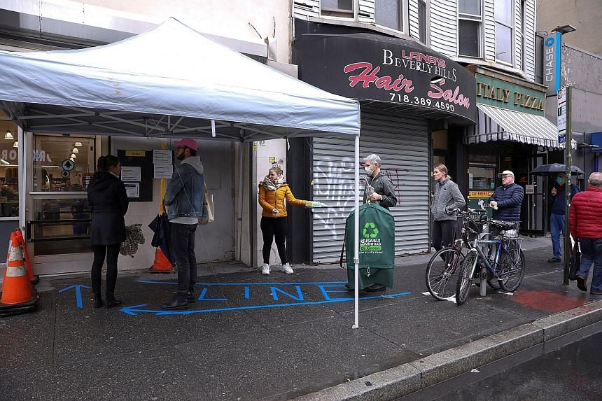 People practising social distancing while waiting in line outside a grocery store in Brooklyn, New York, on Saturday. The death count in the United States has crossed 2,200, more than double the level from two days ago.