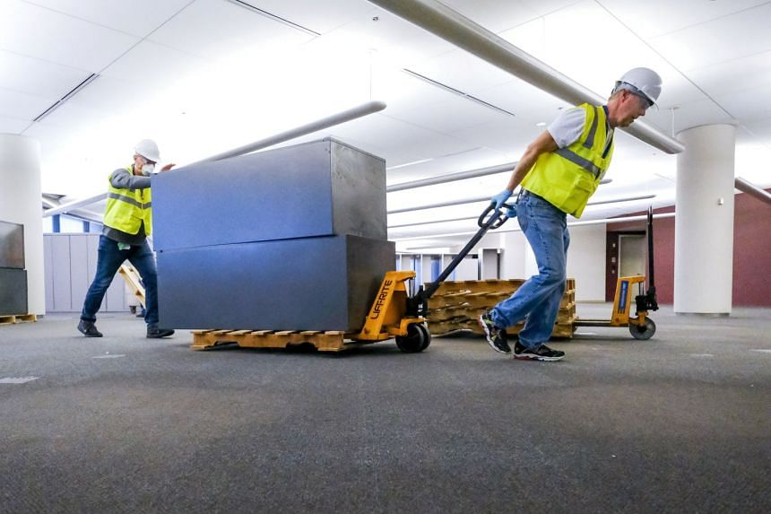 Workers clear furniture from a floor the building that General Motors and Ventec Life Systems are converting into use for the production of Ventec ventilators in the US on March 28, 2020.