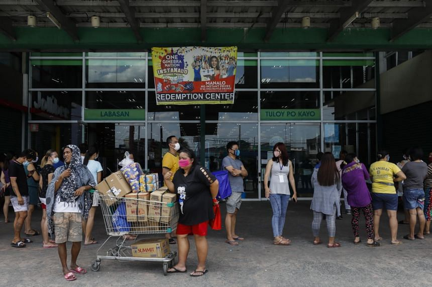 People queue outside a supermarket in Quezon City, in the Metro Manila region of the Philippines, on March 27, 2020.