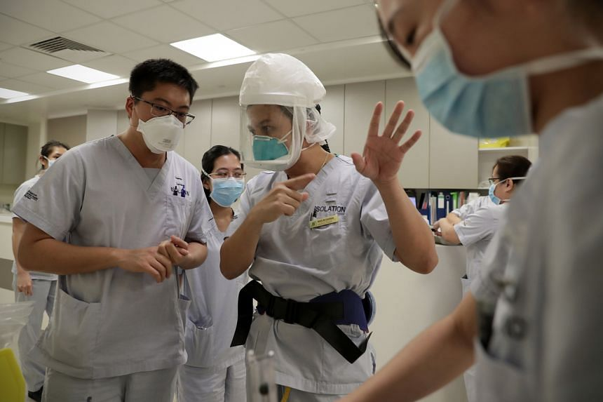 Healthcare workers discuss necessary procedures as they prepare to intubate a suspected Covid-19 patient in the isolation room at Singapore General Hospital.