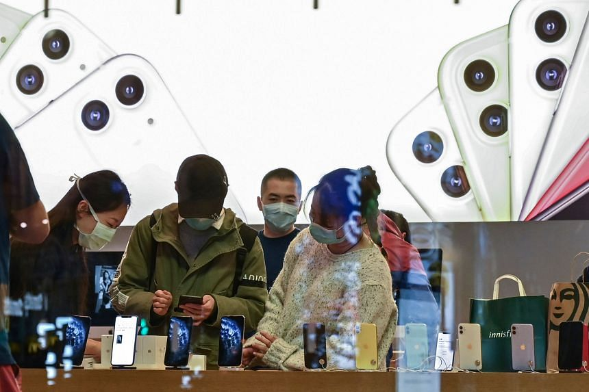 Customers and workers wearing facemasks in an Apple store in Shanghai, China, on March 16, 2020.