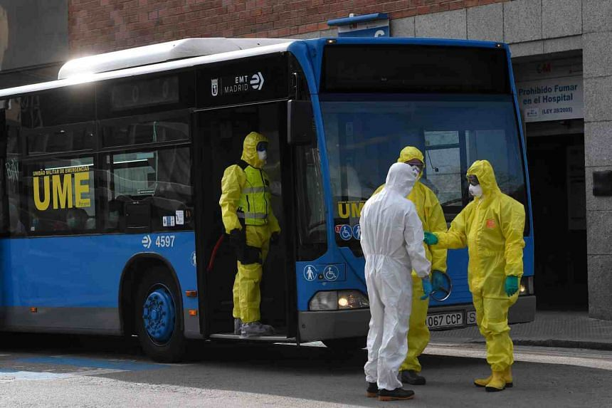 Members of Spanish Military Emergencies Unit (UME) wearing protective suits stand outside a bus used to transport patients from the San Carlos Clinic Hospital to a temporary hospital set-up for coronavirus patients at the Ifema convention and exhibit