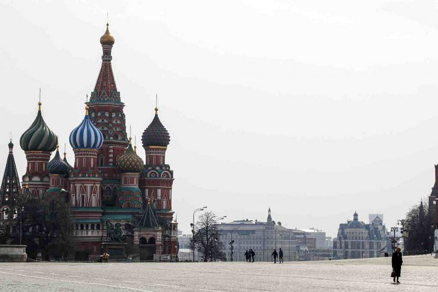 People walk near the cathedral of Vasily the Blessed in the Red Square in Moscow on March 29, 2020.