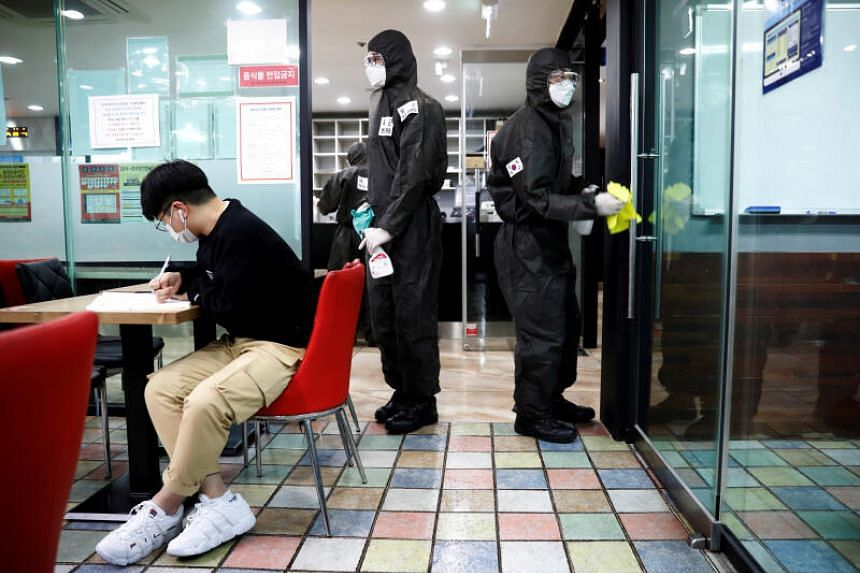 South Korean soldiers clean doors with disinfectant at a cram school in Daegu, South Korea, on March 15, 2020.