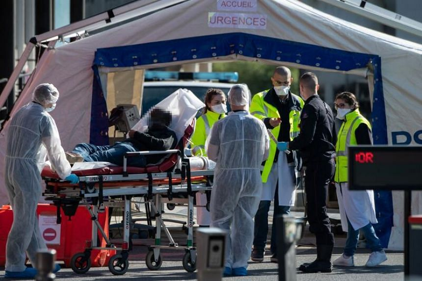 Doctors tend to a patient arriving on a stretcher at the reception of the emergency room set up in a tent, in a courtyard of the Henri Mondor Hospital in Creteil, near Paris, on March 30, 2020.