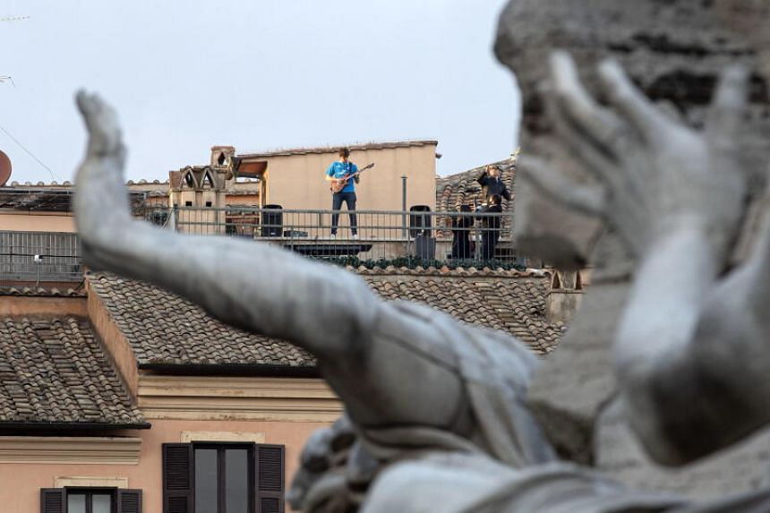 People play music from a rooftop in Navona square during an extended lockdown due to the coronavirus outbreak in Rome, Italy, on March 30, 2020.