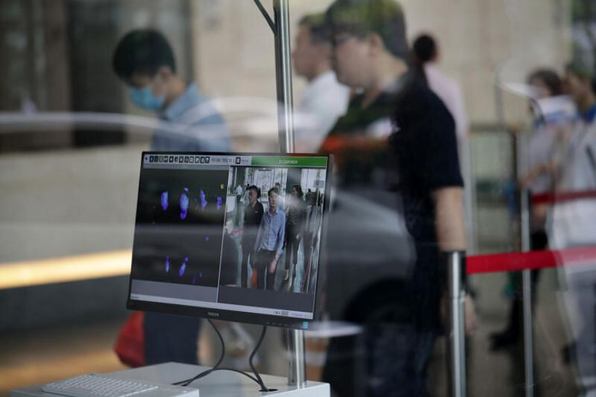Office workers going through a thermal scanner at MBFC Towers on March 11, 2020.