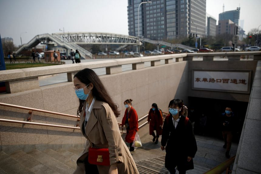 People wearing face masks exit a subway station in Beijing on March 30, 2020.