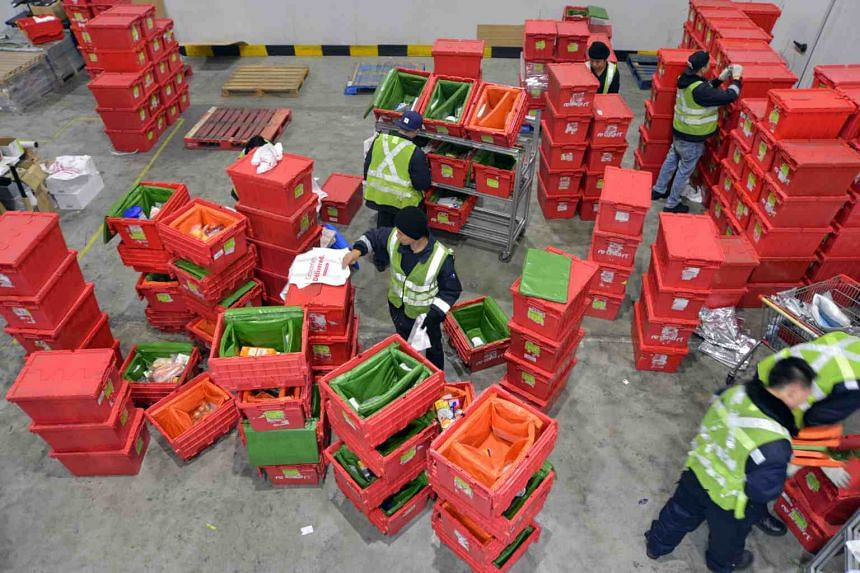 Staff at work at Singapore online grocery store RedMart. Redmart said it is looking into hiring more workers to increase fulfilment capacity.