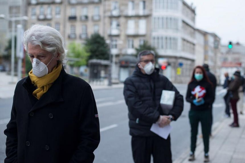 People wearing protective face masks wait in a queue in front of a post office in Ourense, northwestern Spain, on March 30, 2020.