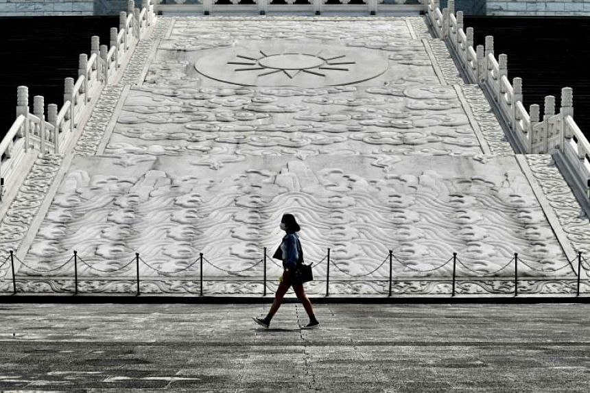 A woman wearing a face mask walks in front of Chiang Kai-shek Memorial Hall in Taipei, Taiwan, on March 31, 2020.