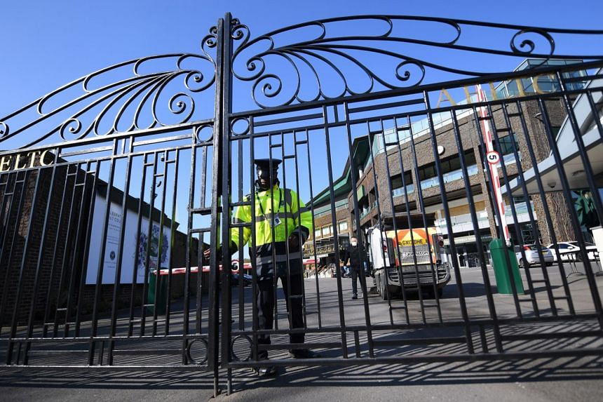 A security guard at the gates of the All England Lawn Tennis Club in Wimbledon, London, April 1, 2020.