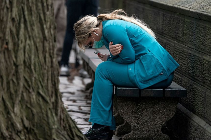 A healthcare worker sits on a bench near New York's Central Park, March 30, 2020.