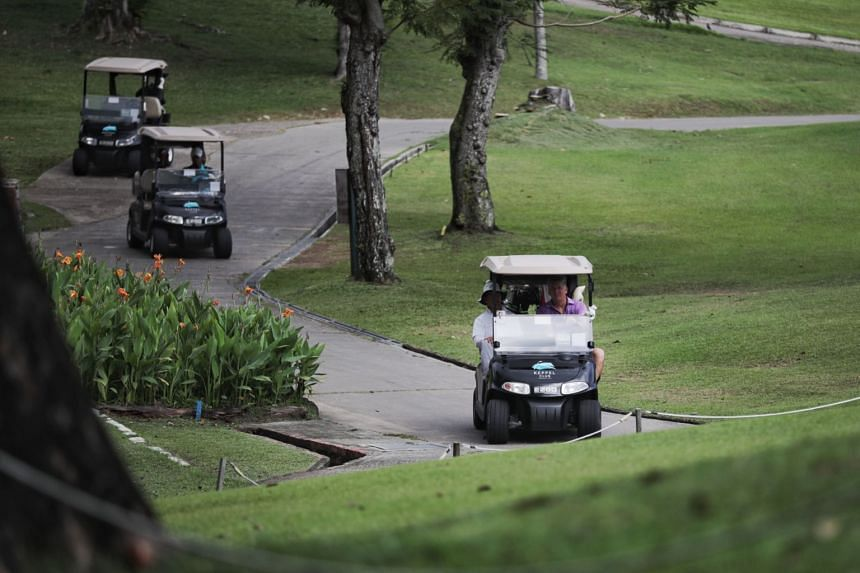 Golfers travel in their buggies at the Keppel Club golf course on March 27, 2020.