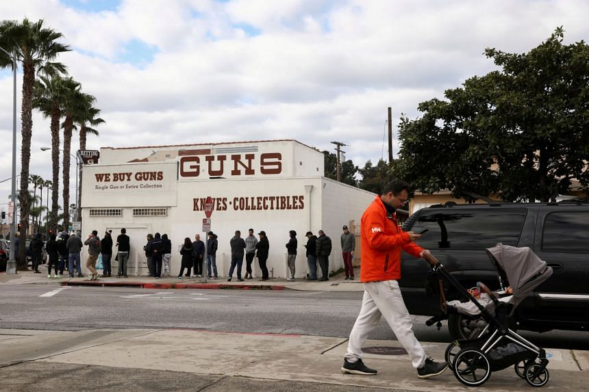A pedestrian pushes a stroller as people wait in line outside a gun store in Culver City, California, on March 15, 2020.
