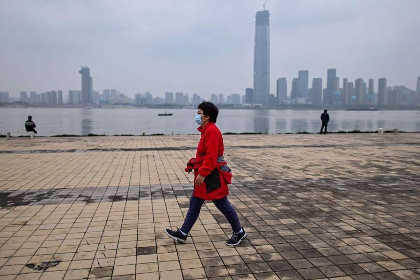 A woman wearing a face mask walks along the Yangtze River on March 31, 2020.