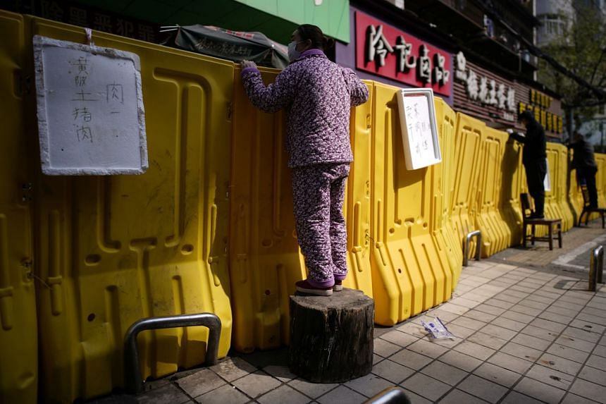 Residents pay for groceries by standing on chairs to peer over barriers in Wuhan, Hubei province, on April 1, 2020.