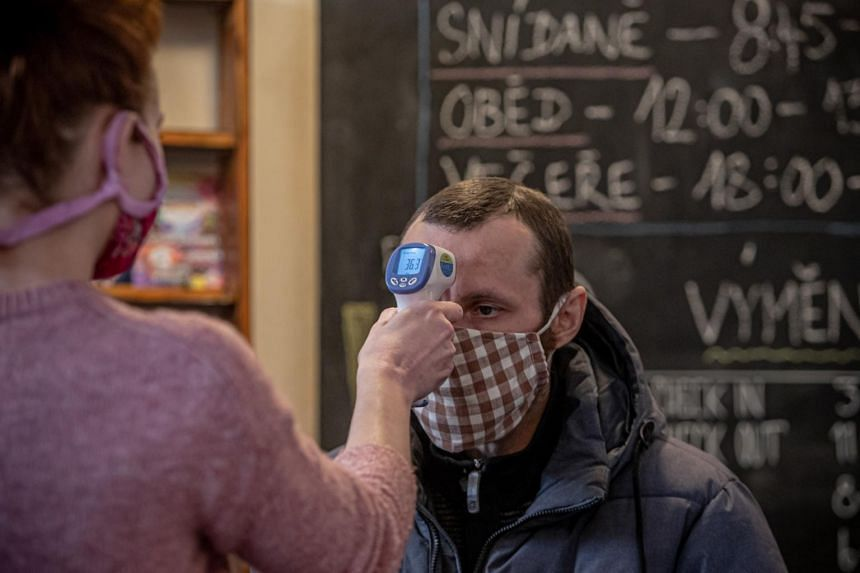 A charity worker measures the body temperature of a man wearing a protective face mask in Prague, Czech Republic, on March 31, 2020.