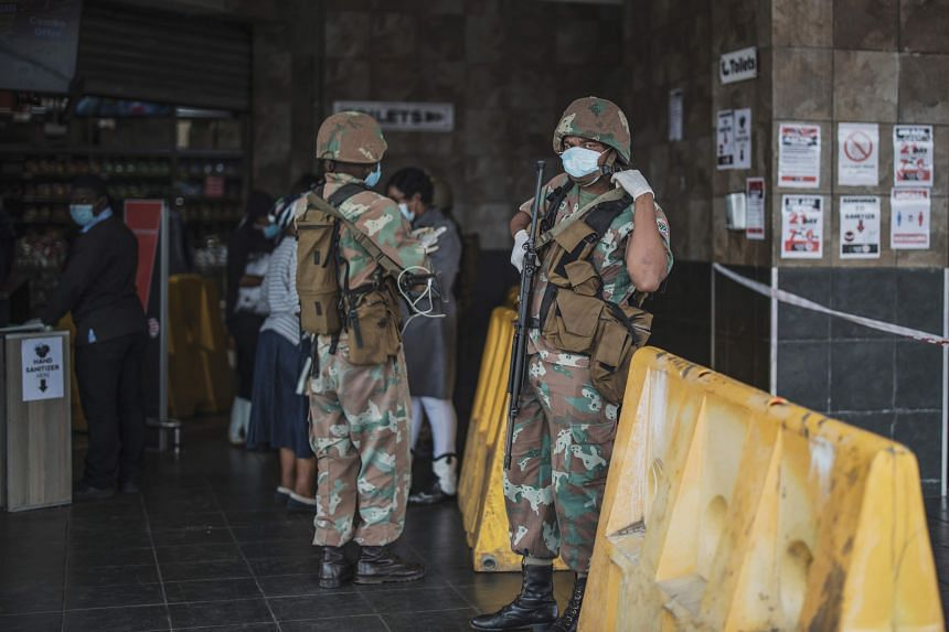 A South African National Defence Force soldier stands at the entrance of a supermarket in Soweto on March 30, 2020.