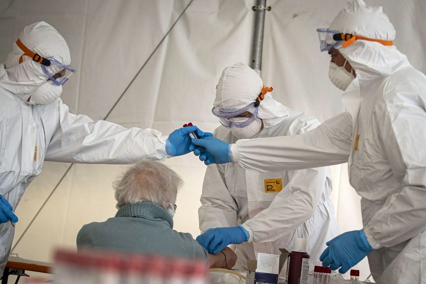 Health personnel perform blood tests and monitoring activities in Nerola, Italy, on March 31, 2020.