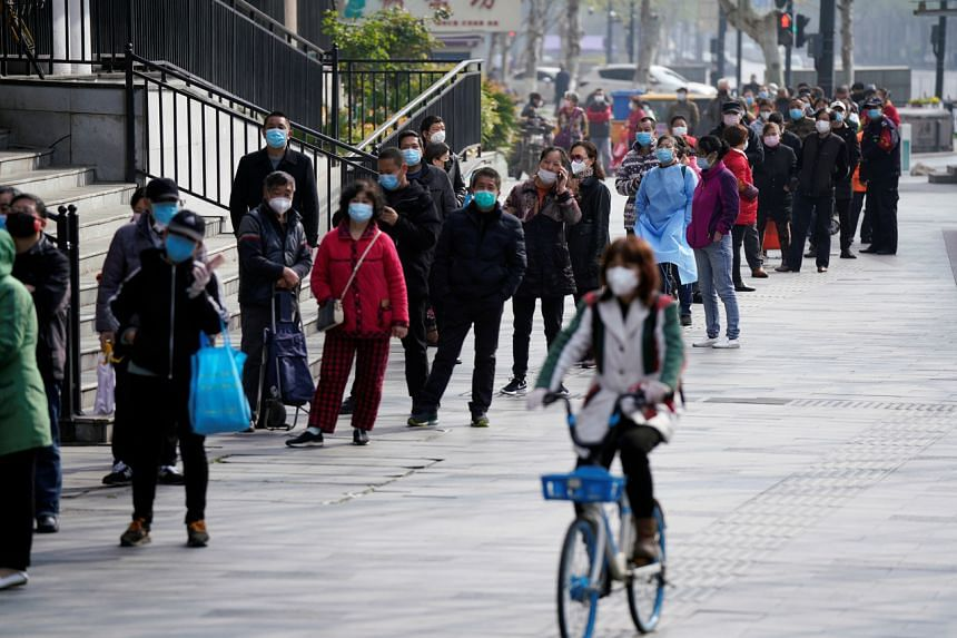 A woman wearing a face mask rides a shared bicycle past people lining up to enter a supermarket in Wuhan on April 1, 2020.