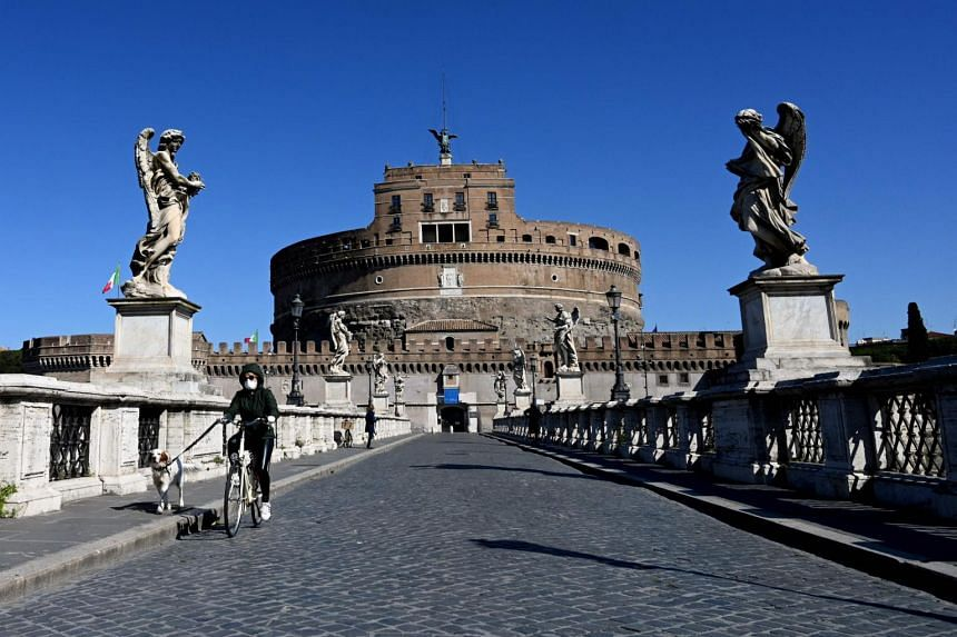 A woman rides a bicycle and walks her dog across Sant'Angelo bridge in Rome, on April 1, 2020.