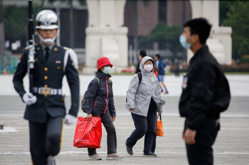 Tourists wearing face masks at the Chiang Kai Shek Memorial Hall in Taipei on March 11, 2020.