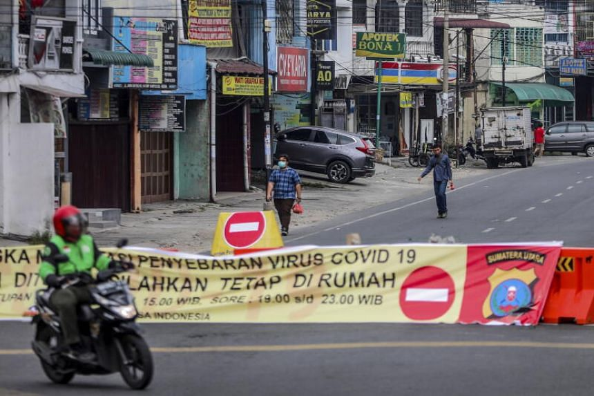 People walking on a closed road in Medan, North Sumatra, Indonesia, on April 1, 2020.