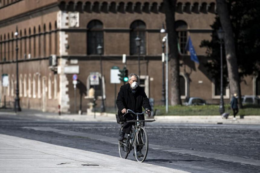 A man wearing a mask cycles in Rome on March 31, 2020.