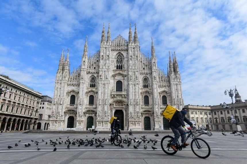 Two food delivery cyclists ride across a deserted Piazza Duomo in Milan, on March 31, 2020.