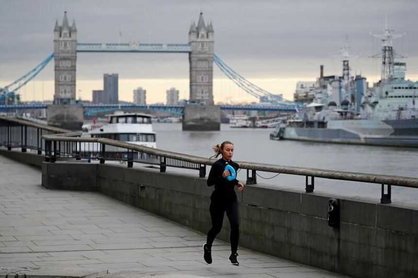 A woman jogs along the bank of the River Thames in London, on March 30, 2020.