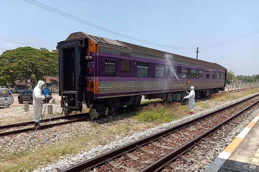 Workers disinfect a train car in Thap Sakae, Thailand, on March 31, 2020.