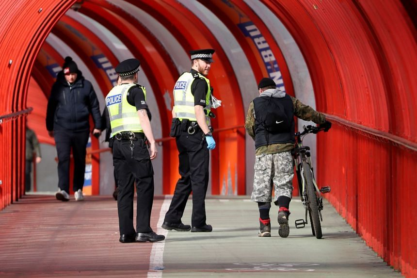 Police talk to cyclists in Glasgow, Scotland, amid the spread of coronavirus in Britain, March 31, 2020.