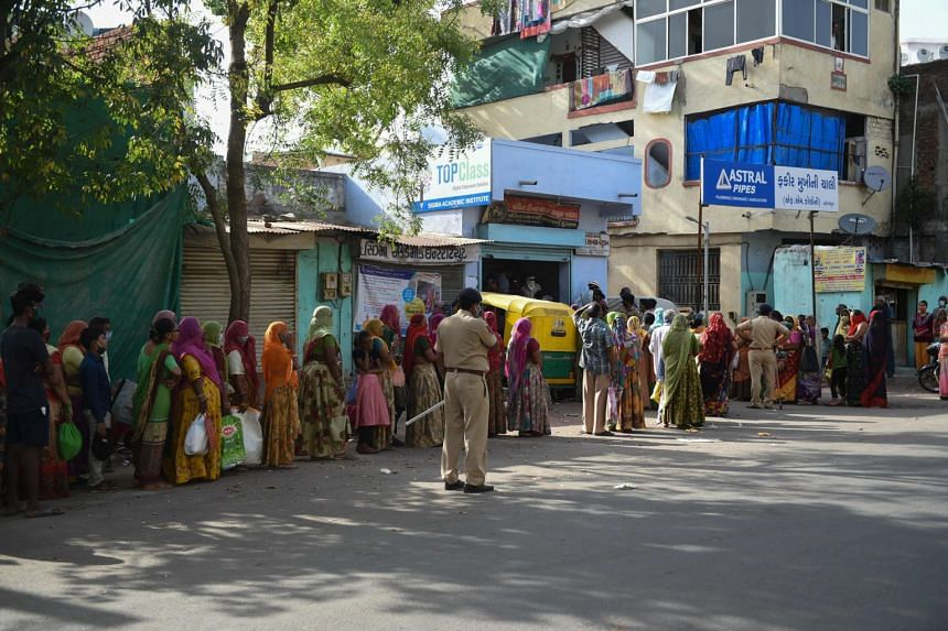 People queue to receive a food ration in Ahmedabad, India, on April 1, 2020.