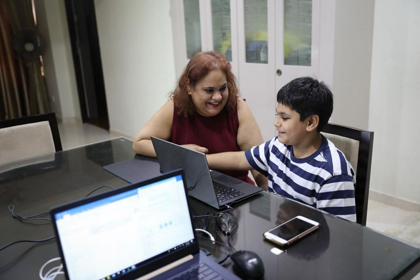 Mrs Janeshtha Vaswani, 47, helping her Primary 2 son with his home-based learning on Wednesday (April 1), the latest measure implemented by the Education Ministry to get students and families better prepared during the coronavirus outbreak.