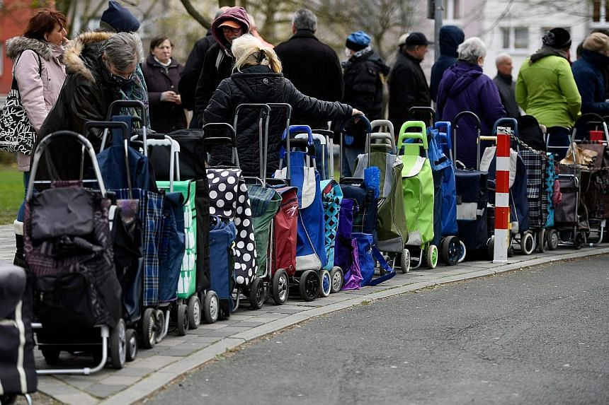 Recipients of a German food bank waiting to pick up supplies earlier this week. Fears are growing that the downturn could be far more punishing than initially feared, as governments intensify restrictions on business to halt the spread of the pandemi