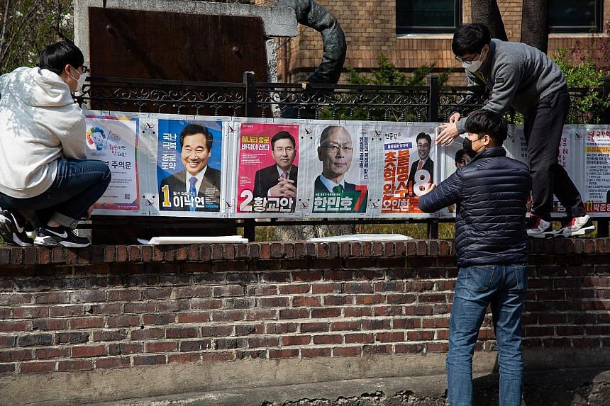 Officials of the National Election Commission putting up campaign posters in Seoul yesterday. South Koreans go to the polls on April 15 to elect a new National Assembly, the country's Parliament. PHOTO: EPA-EFE Independent candidate Lee Heng-suk, dre